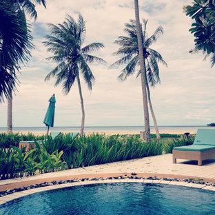 Foto de piscina natural, asiática, pequeña, redondeada, en patio delantero, con entablado