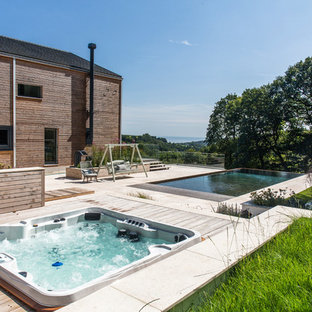 Inspiration for a farmhouse back rectangular infinity swimming pool in Devon with a hot tub.
