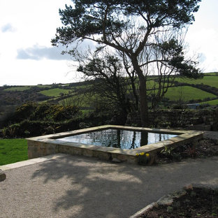 This is an example of a traditional pool in Surrey with a hot tub and gravel.