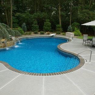 Imagen de piscina con fuente alargada, clásica, de tamaño medio, a medida, en patio trasero, con adoquines de ladrillo