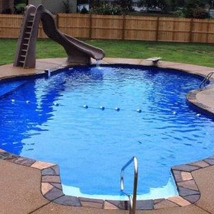 Modelo de piscina con tobogán alargada, clásica, de tamaño medio, a medida, en patio trasero, con granito descompuesto