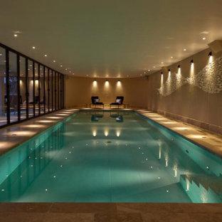 Imagen de piscina alargada, grande, interior y rectangular, con privacidad y adoquines de piedra natural