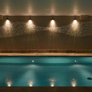 Foto de piscina alargada, grande, interior y rectangular, con privacidad y adoquines de piedra natural