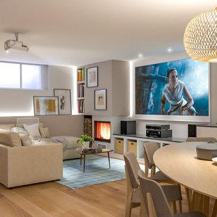 Idée de décoration pour un grand sous-sol nordique enterré avec salle de cinéma, un mur multicolore, un sol en bois clair, une cheminée ribbon, un manteau de cheminée en plâtre et un plafond décaissé.