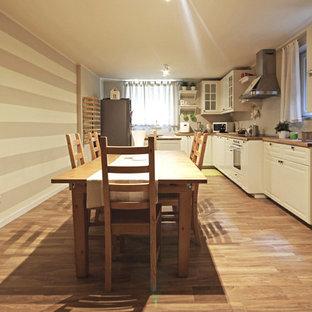 Réalisation d'un grand sous-sol champêtre donnant sur l'extérieur avec un mur multicolore, un sol en bois peint, une cheminée standard, un manteau de cheminée en béton et un sol marron.