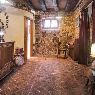 Esempio di una taverna mediterranea di medie dimensioni con sbocco, pareti multicolore, pavimento in mattoni e pavimento marrone