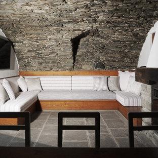 Aménagement d'un grand sous-sol montagne donnant sur l'extérieur avec un mur blanc, un sol en calcaire, une cheminée standard, un manteau de cheminée en pierre et un sol gris.