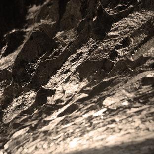 Réalisation d'un grand sous-sol chalet donnant sur l'extérieur avec un mur blanc, un sol en calcaire, une cheminée standard, un manteau de cheminée en pierre et un sol gris.