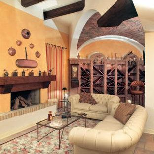 Cette photo montre un grand sous-sol chic enterré avec un mur jaune, un sol en carrelage de porcelaine, une cheminée standard et un manteau de cheminée en brique.
