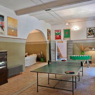 Idée de décoration pour un grand sous-sol design avec un mur multicolore, un sol en brique et un sol rose.