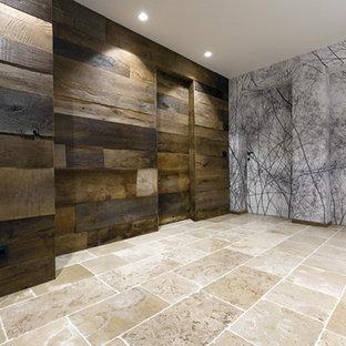 Aménagement d'un grand sous-sol moderne donnant sur l'extérieur avec un mur marron, un sol en calcaire, une cheminée d'angle, un manteau de cheminée en bois et un sol beige.
