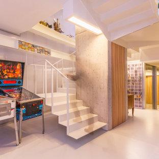 Immagine di una taverna minimal con pareti bianche e pavimento bianco