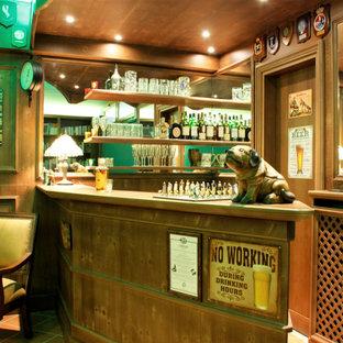 Exemple d'un grand sous-sol chic donnant sur l'extérieur avec un bar de salon, un mur vert, un sol en carreau de terre cuite et boiseries.