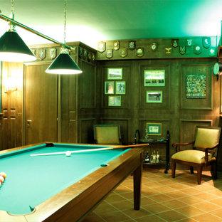 Cette image montre un grand sous-sol traditionnel donnant sur l'extérieur avec un bar de salon, un mur vert, un sol en carreau de terre cuite et boiseries.