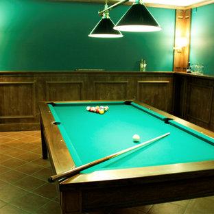 Réalisation d'un grand sous-sol tradition donnant sur l'extérieur avec un bar de salon, un mur vert, un sol en carreau de terre cuite et boiseries.