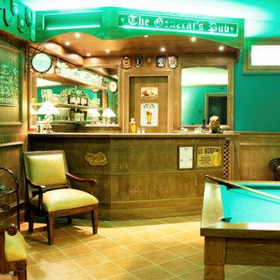 Aménagement d'un grand sous-sol classique donnant sur l'extérieur avec un bar de salon, un mur vert, un sol en carreau de terre cuite et boiseries.