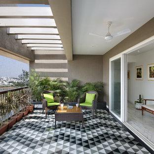 Esempio di terrazze e balconi design con un giardino in vaso, un tetto a sbalzo e parapetto in metallo