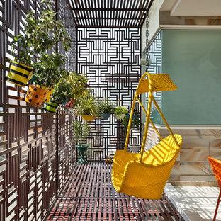 Esempio di piccoli terrazze e balconi contemporanei con un giardino in vaso, parapetto in metallo e un tetto a sbalzo