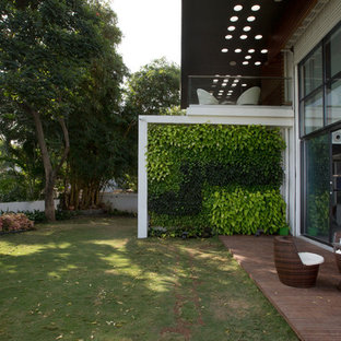 Photo of a contemporary backyard deck in Pune with a vertical garden and no cover.