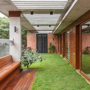 Esempio di terrazze e balconi minimalisti con un tetto a sbalzo e parapetto in materiali misti
