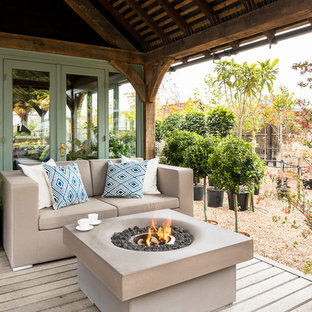 This is an example of a medium sized farmhouse terrace and balcony in London with a fire feature and a roof extension.