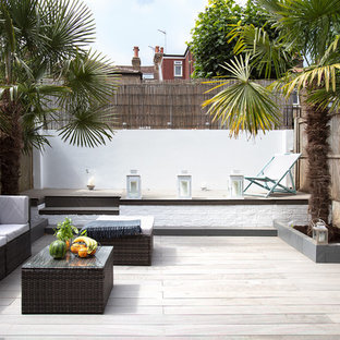 This is an example of a medium sized contemporary back terrace and balcony in London with a potted garden.