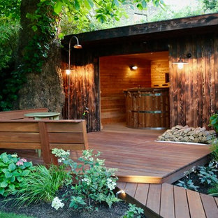 Photo of a large tropical backyard deck in London with an outdoor shower.