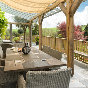 Example of a large classic backyard deck design in Devon with a pergola