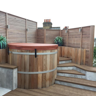 This is an example of a small contemporary rooftop deck in London with an awning and with privacy feature.