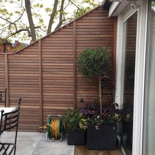 Cette image montre une terrasse design avec un auvent et des solutions pour vis-à-vis.