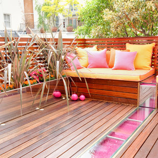 Large trendy backyard deck container garden photo in London