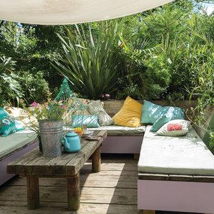 Ispirazione per una terrazza boho chic dietro casa con un giardino in vaso e un parasole