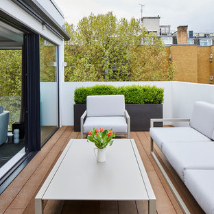 This is an example of a medium sized contemporary terrace in London with a potted garden and no cover.