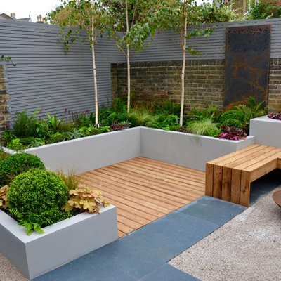 Example of a small trendy backyard deck design in London with a fire pit and no cover