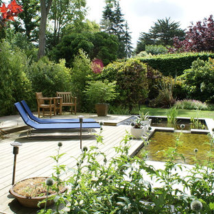 Inspiration for a large timeless backyard water fountain deck remodel in Hertfordshire with no cover