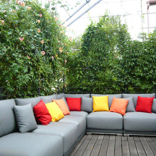 This is an example of a large contemporary rooftop deck in Munich with a vertical garden and a pergola.