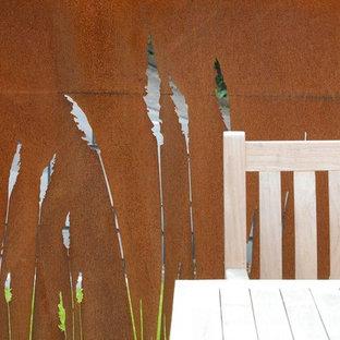 Bild på en mellanstor funkis terrass på baksidan av huset, med en vertikal trädgård