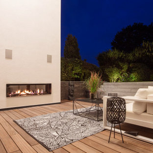 Deck - large contemporary backyard deck idea in Dortmund with a fireplace and no cover