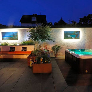 Large tuscan backyard deck photo in Frankfurt with a fire pit and no cover