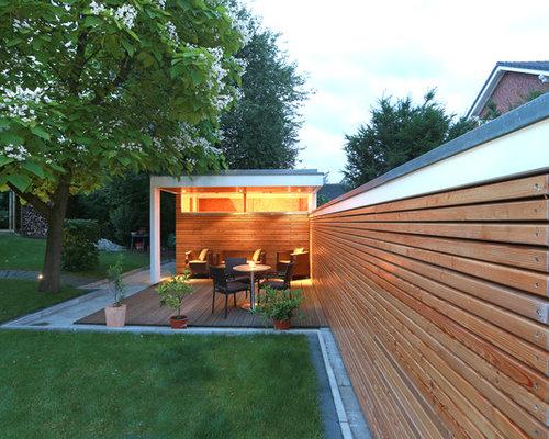 Mittelgroße, Überdachte Moderne Terrasse Hinter Dem Haus Mit Kübelpflanzen  In Sonstige