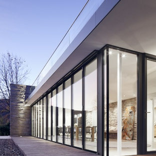 Esempio di terrazze e balconi minimal di medie dimensioni e dietro casa con un tetto a sbalzo