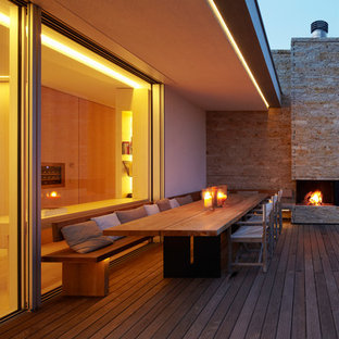 Photo of a large scandi back terrace in Munich with a fire feature and a roof extension.