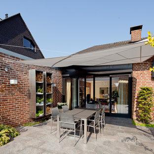 Foto de terraza contemporánea, de tamaño medio, en patio lateral, con brasero y toldo