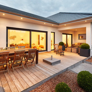 Large danish backyard deck photo in Nuremberg with a fire pit and no cover