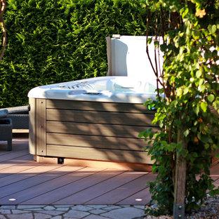 Aménagement d'une terrasse arrière méditerranéenne avec jupe de finition et aucune couverture.