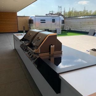 Large trendy courtyard outdoor kitchen deck photo in Berlin