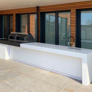 Large trendy courtyard outdoor kitchen deck photo in Essen