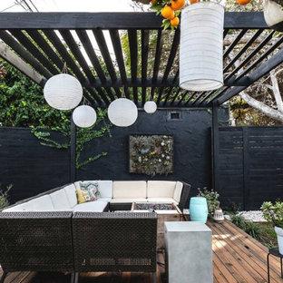Idée de décoration pour une grande terrasse arrière bohème avec des solutions pour vis-à-vis et une pergola.