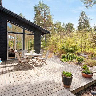 Example of a mid-sized danish backyard deck design in Stockholm with no cover