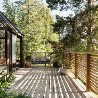 Example of a mid-sized mountain style backyard deck design in Stockholm